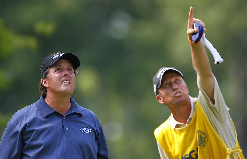 Phil Mickeslon of the US (L) and his caddie Jim Mackay (R) look towards something in the sky on the eighth tee during the third day of the US Open Golf Championship at Winged Foot Golf Club in Mamaroneck, New York Saturday, 17 June 2006. .