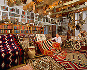 0108-1000 ~  Copyright: George H.H. Huey ~ Bill Malone, trader, in Rug Room, with historic and modern Navajo Indian weavings.  Founded by John Lorenzo Hubbell in 1876. Still an active trading post today.  Hubbell Trading Post National Historic Site, Arizona