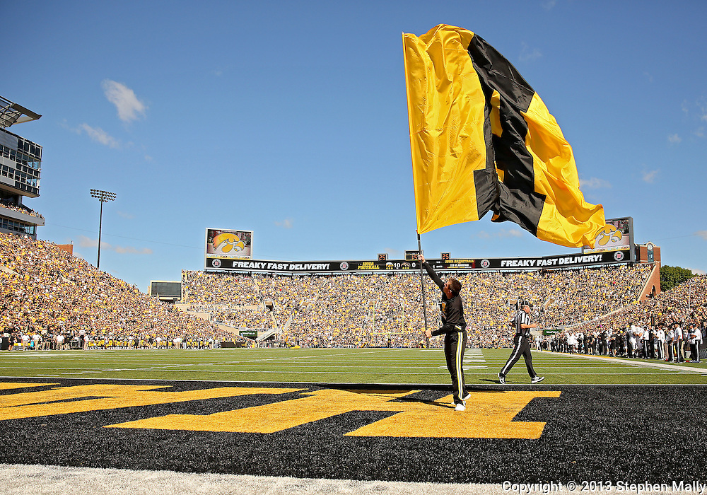 "September 21 2013: An Iowa Hawkeyes cheerleader raises an ""A"" flag after a touchdown score during the first quarter of the NCAA football game between the Western Michigan Broncos and the Iowa Hawkeyes at Kinnick Stadium in Iowa City, Iowa on September 21, 2013. Iowa defeated Western Michigan 59-3."
