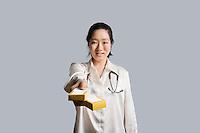 Portrait of a young female doctor giving medicine boxes