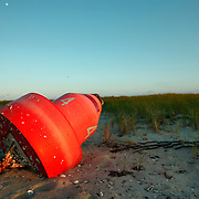 A marker buoy lies washed up on a beach of Portsmouth Island, NC. Located in the North Core Banks, just southwest of  Ocracoke Island. Portsmouth Village was established by North Carolina's Colonial Assembly in 1753, but the island's last permanent residents left in 1971, and is now uninhabited.