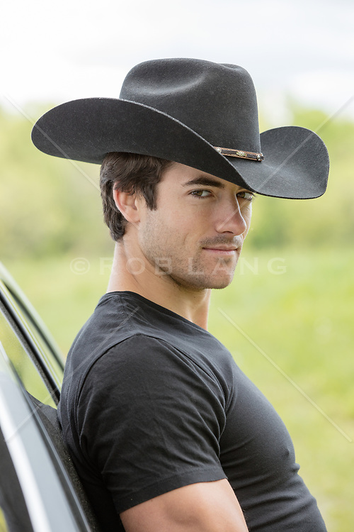 portrait of a cowboy leaning on a truck