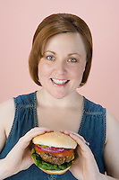 Mid-adult woman holding hamburger
