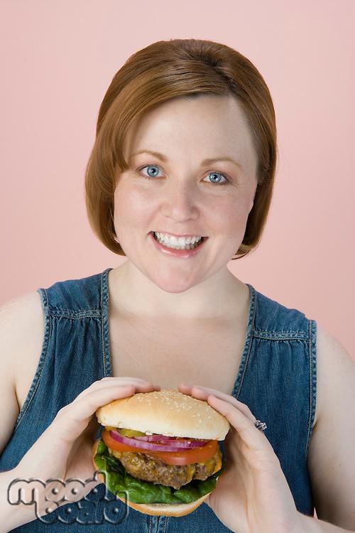 Mid-adult woman holding hamburger