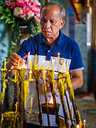 "30 DECEMBER 2017 - BANG KRUAI, NONTHABURI, THAILAND:  A man lights prayer candles to make merit for the new year at Wat Ta Khien, about 45 minutes from Bangkok in Nonthaburi province. The temple is famous for the ""floating market"" on the canal that runs past the temple and for the ""resurrection ceremonies"" conducted by monks at the temple.      PHOTO BY JACK KURTZ"