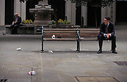 With litter on the ground nearby and with handwriting proclaiming the far-right BNP (British National Party) saving England, a businessman smokes on a bench while lost in thought , on 16th June 1994, in London, England.