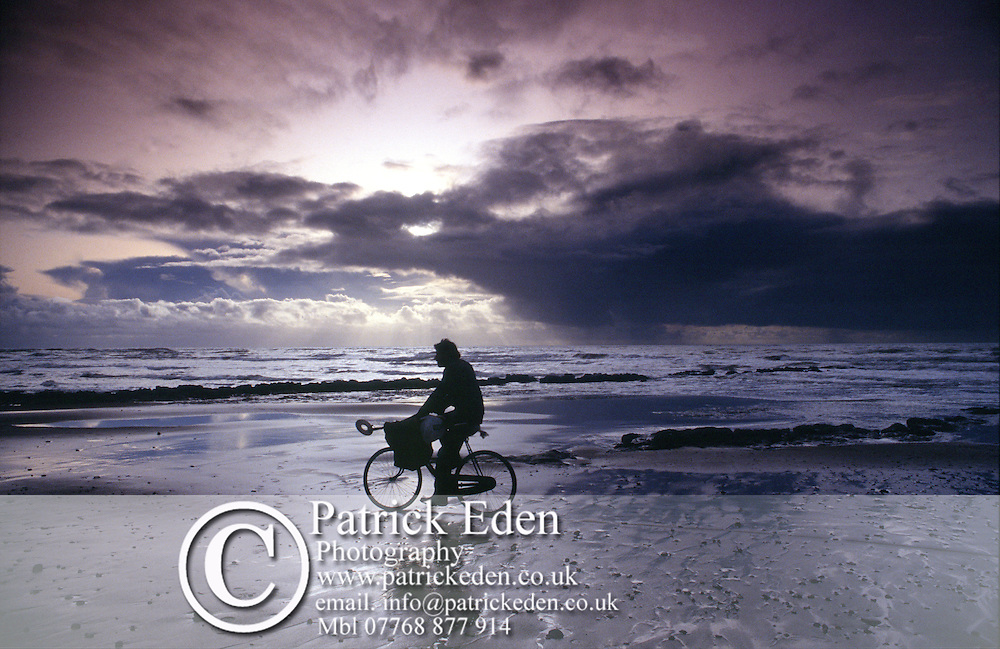 Man with metal detector cycling along beach Photographs of the Isle of Wight by photographer Patrick Eden photography photograph canvas canvases