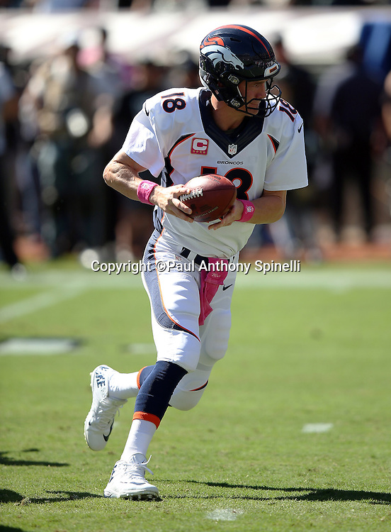 Denver Broncos quarterback Peyton Manning (18) hands off the ball on a running play during the 2015 NFL week 5 regular season football game against the Oakland Raiders on Sunday, Oct. 11, 2015 in Oakland, Calif. The Broncos won the game 16-10. (©Paul Anthony Spinelli)