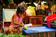 a young girl cutting a fruit with a huge knife, phnom penh, cambodia