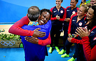Aug 19, 2016; Rio de Janeiro, Brazil;  United States United States goalkeeper Ashleigh Johnson (13) embraces coach Adam Krikorian in the women's water polo medal ceremony at Olympic Aquatics Stadium during the Rio 2016 Summer Olympic Games. Mandatory Credit: Peter Casey-USA TODAY Sports