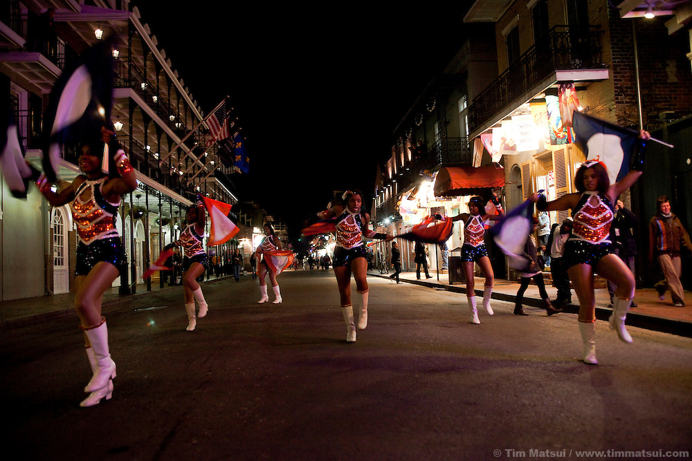 A prep school marching band performs at night in the French Quarter of New Orleans.