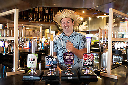 © Licensed to London News Pictures. 04/07/2020. Perranporth, UK. Tommy Job - manager of the Watering Hole, the UK's only bar on the beach - pours a pint of beer shortly after opening time. Today marks a lift in COVID-19 restrictions, as pubs are allowed to open, whilst customers must still follow social distancing guidelines. Tens of thousands of tourists are due to arrive in Cornwall over this weekend, as overnight stays within England are also allowed. Photo credit : Tom Nicholson/LNP
