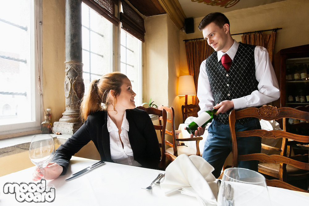 Waiter showing wine bottle to female customer at table in restaurant