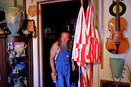"A resident of Erick, Oklahoma, pauses during a tour of his home, filled with Route 66 nostalgia and Americana. He declared Erick ""Redneck capital of the world."" Erick is a semi-ghost town on Route 66 in Eastern Oklahoma."