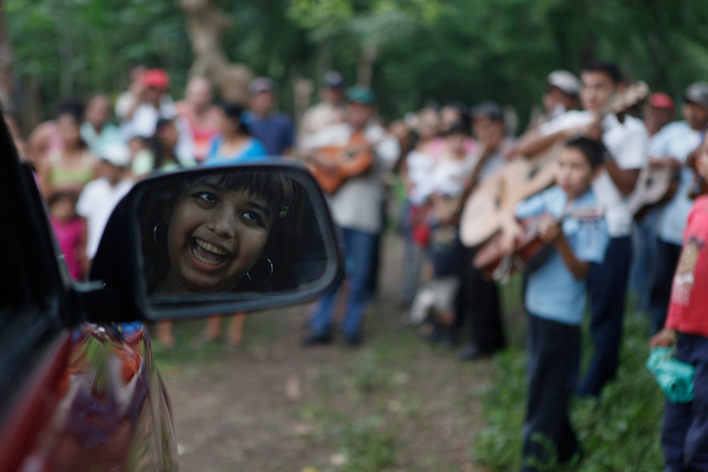 In this photo taken on Monday, Aug. 29, 2011. Maria Jose Martinez, reflected in a side-view mirror,  smiles while her relatives and neighbords wait for her arrival at 'La Cuchilla' after traveling with her parents after been temporaly discharged from 'La Mascota' children hospital, Matagalpa, Nicaragua. A Leukemia patient Maria Jose was admitted for her treatment at La Mascota Hospital in May. 10 of 2011 until August. 29 of 2011, during that period she stayed one month at the intensive care unit. The Association of Parents of children with leukemia and Cancer in Nicaragua, Mapanica, have been organizing for their third year the 15 year old celebration of young girls that have been struggling with the cancer and they still are battling to win this fight against some type of cancer and leukemia at the Childrens hospital La Mascota, in Managua, Nicaragua. (Esteban Felix)