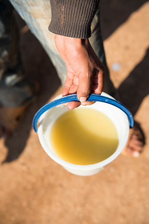A Syrian refugee in the camp for displayed persons in Atmeh, Syria, holds a bowl of basic soup served to him and many other refugees. He complained about its quality, and the general lack of aid to the camp.