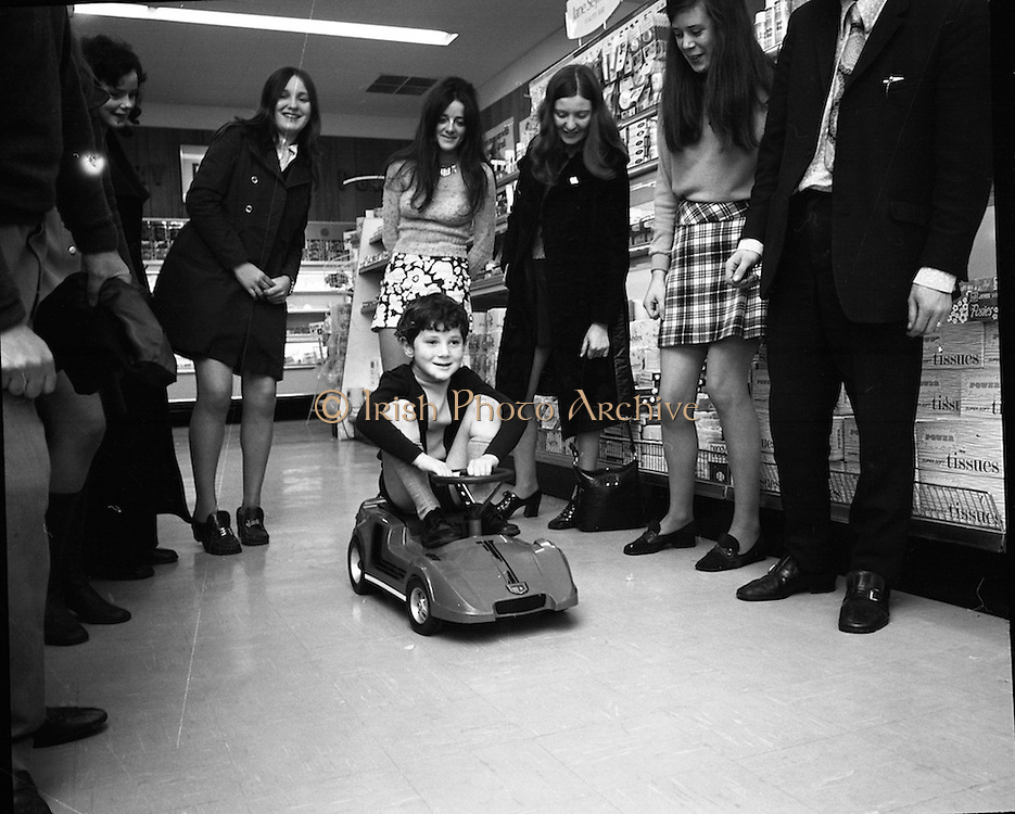Electric Car Race at Supermarkets.<br /> 1971.<br /> 30.10.1971.<br /> 10.30.1971.<br /> 30th October 1971.<br /> Elect car races were held in Powers Supermarkets in Stillorgan,Blackrock Co Dublin and in Bray Co Wicklow.<br /> <br /> Image shows this young man as he sets off in the electric car watched by family and store staff.