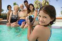 Girl (10-12) in swimming pool video taping brother (13-15) parents and grandparents portrait.