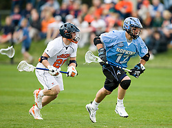 Johns Hopkins midfielder Stephen Peyser (12) wins a faceoff against UVA.  The #2 ranked Virginia Cavaliers defeated the #6 ranked Johns Hopkins Blue Jays 13-12 in overtime at the University of Virginia's Klockner Stadium in Charlottesville, VA on March 22, 2008.  The loss, in front of a record UVA crowd of 7,500, was the third consecutive overtime defeat for Hopkins, the defending national champions.