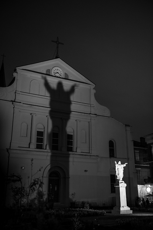 A statue of Jesus casts a shadow against the facade of the Cathedral of St. Louis at night in New Orleans, Louisiana