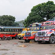Chicken buses parked behind the Mercado Municipal (town market) in Antigua, Guatemala. From this extensive central bus interchange the routes radiate out across Guatemala. Often brightly painted, the chicken buses are retrofitted American school buses and provide a cheap mode of transport throughout the country.