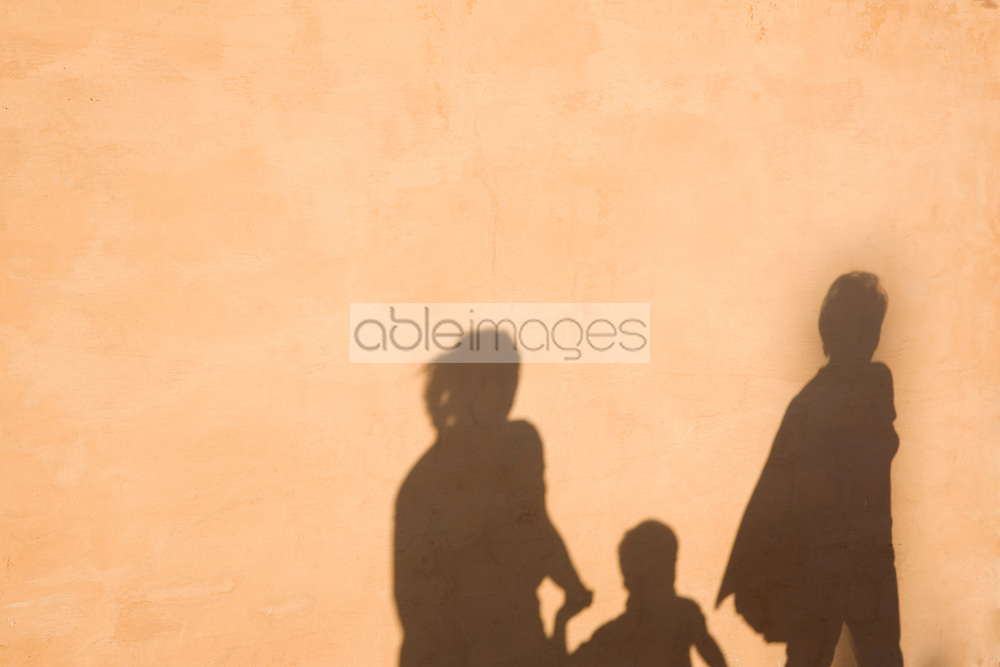 Shadow on a wall of two women and a boy walking