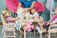 Midsection of girl pretending to have tea party with her dolls
