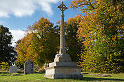 War memorial for The Great War 1914-1918 - World War I and World War II 1939-1945  alongside graves in traditional graveyard of St Mary's Church, Swinbrook commemorating those who died from the parish of Swinbrook and Widford, Oxfordshire, UK