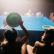 KUMAMOTO, JAPAN - APRIL 19: Young boys having fun in bathing facility set up by the Self-Defense Forces outside the Mashiki Town Gymnasium evacuation center on April 19, 2016 in Mashiki, Kumamoto, Japan. <br /> <br /> Photo: Richard Atrero de Guzman