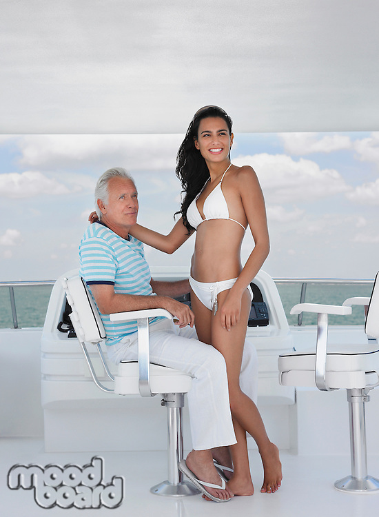 Middle-aged man and young woman at helm of yacht