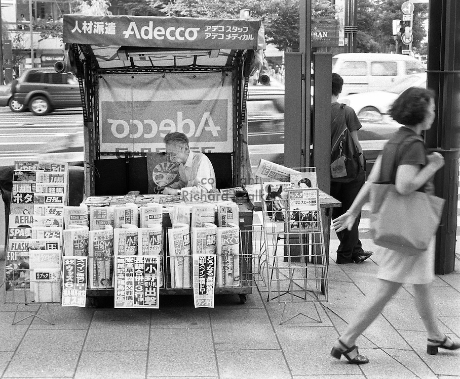 A newsstand vendor fans himself in the sweltering summer heat on a Ginza street corner. Ginza, Tokyo, August, 1998. By Richard Walker