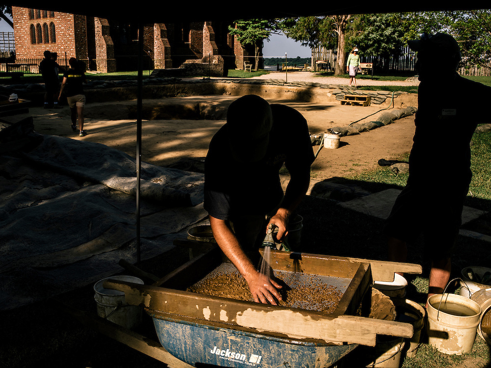 Archaeologist intern Bob Chartrand, left, sifts through dirt and pieces of artifacts discovered in a new dig site at the Jamestown settlement in Va.