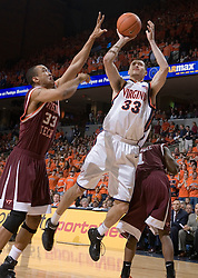 Virginia Cavaliers forward Jason Cain (33) shoots over Virginia Tech Hokies forward Coleman Collins (33).  The Virginia Cavaliers Men's Basketball Team defeated the Virginia Tech Hokies 69-56 at the John Paul Jones Arena in Charlottesville, VA on March 1, 2007.