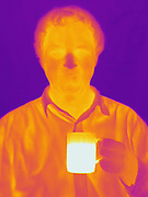 A Thermogram of a man with coffee.  This image is part of a series and has a corresponding visible light image.  The different colors represent different temperatures on the object. The lightest colors are the hottest temperatures, while the darker colors represent a cooler temperature.  Thermography uses special cameras that can detect light in the far-infrared range of the electromagnetic spectrum (900?14,000 nanometers or 0.9?14 µm) and creates an  image of the objects temperature..