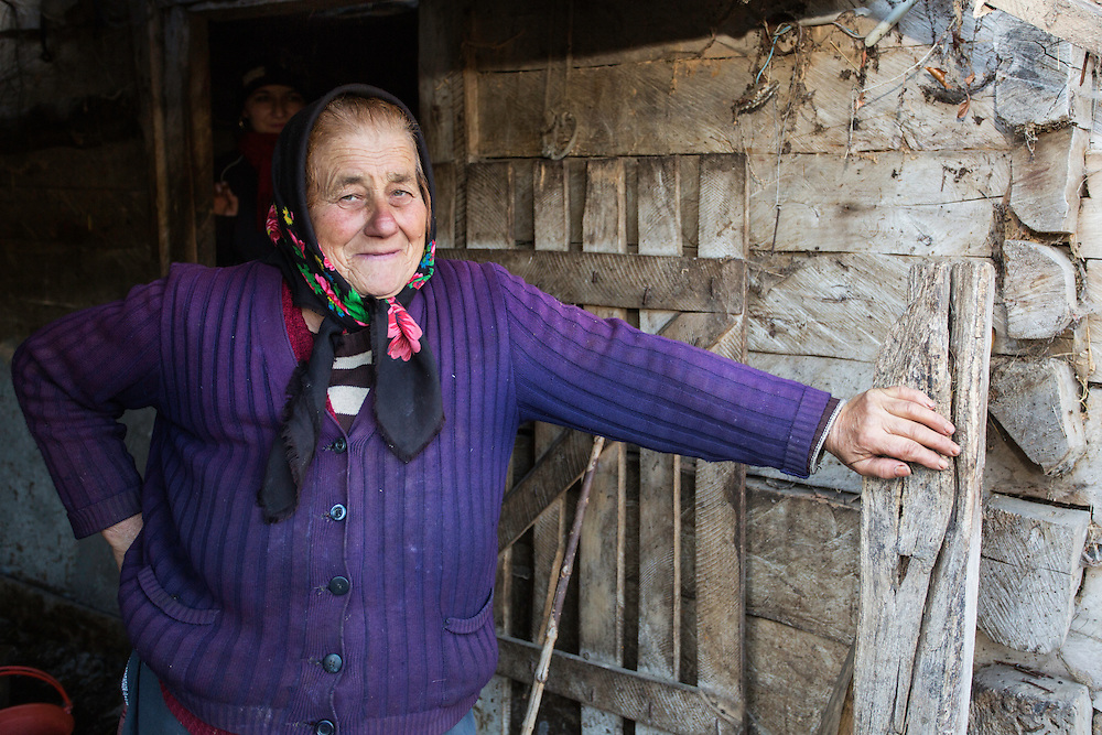 Farmer lady at the entrance to the stable at her house in the village of Isverna. Geoparcul Platoul Mehedinți, Romania.