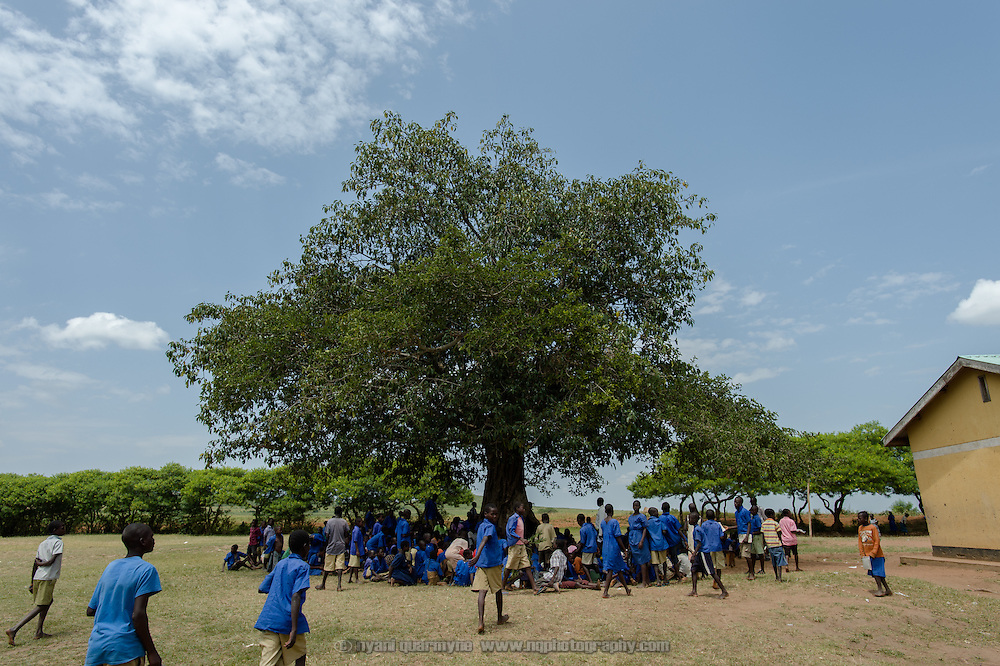 Students gather under a tree to listen to the Health Prefects speak about general hygiene and sanitation issues as well as menstrual hygiene at Aputiri Primary School in Eastern Uganda on 31 July 2014. The school participates in a Menstrual Health Management program supported by Plan International, which is aimed at both boys and girls.