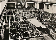 Registry Room of the main building, with queueing immigrants waiting to be processed, photograph, c. 1910, displayed in the Ellis Island Immigration Museum, in the main building on Ellis Island, the immigration processing centre for the United States from 1892 to 1954, at the mouth of the Hudson river in New York City, NY, USA. The registry hall was designed by William Alciphron Boring and Edward Lippincott Tilton and built early 20th century in French Renaissance style. It measures 61x30m and was used for primary inspections, with adjoining rooms used as dormitories and offices. Ellis Island and its Immigration Museum are part of the Statue of Liberty National Monument and are managed by the National Park Authority. Picture by Manuel Cohen