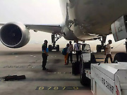 A couple who missed their flight and ran onto the runway with their luggage and prevented the plane from taking off.<br /> <br /> The couple were to catch a 9:30am Air China flight from<br /> Beijing to  Shanghai, but they were left stranded in the Beijing International Airport after the boarding gates closed.<br /> <br /> The bridge had  already been removed, but refusing to miss flight , the woman pulled her husband and the pair ran onto the runway, heading towards the plane before it began taxiing.<br /> <br /> they ignored warnings from ground crew  who had no choice but to call airport police.<br /> <br /> The wife, with her cabin luggage in tow, squatted down underneath the aeroplane and tried to convince authorities to let her and her husband on the flight, but the pair were eventually arrested after a delay of about 20 minutes.<br /> <br /> The couple claimed they were not informed of the boarding time, causing them to miss the flight, but their argument was proven invalid after their boarding passes clearly stated both the boarding and take-off times.<br /> <br /> A couple will receive  detention of between 5 to 10 days and will also be fined 500 RMB (57 GBP).<br /> <br /> at present it is unclear if  they will also receive flight bans in the near future.<br /> ©Exclusivepix Media