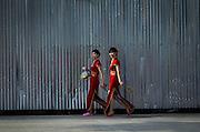Two women wearing traditional qipaos walk past a construction zone in Dongguan.