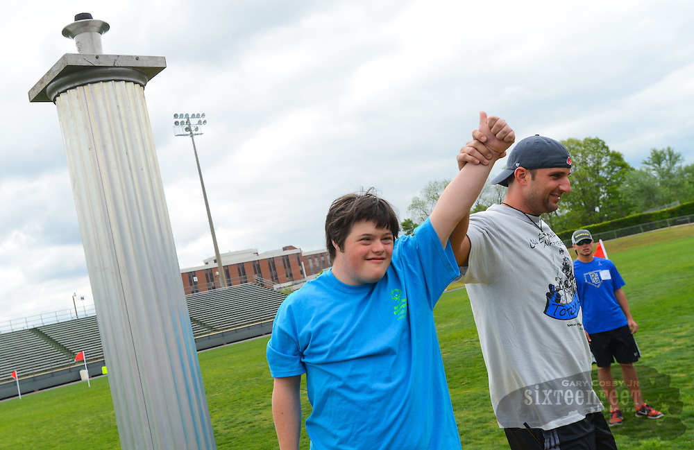 Gary Cosby Jr./Decatur Daily     Travis English and Decatur Police torch runner Kirk Arrington lifts their hands after setting the torch for the games during the Morgan County Special Olympics at Decatur High School Friday, April 25, 2014.