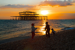 Brighton, UK. Children play on Brighton Beach at sunset. Photo Credit: Hugo Michiels