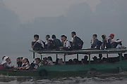 INDONESIA, Palembang : 20 October 2015 Students stand on the wooden boat as they cross the river as the haze shrouded the Ogan river on the way to their school. Forest fires in Sumatra and Borneo that have caused widespread haze in Southeast Asia. Pic by Hairul Akbar / Story Picture Agency