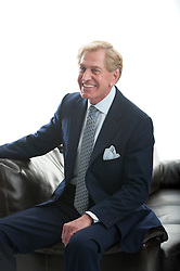 older man in a business suit seated on the edge of a couch