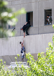 Iranian policemen evacuate a child from the parliament building in Tehran on June 7, 2017 during an attack on the complex. The Islamic State group claimed its first attacks in Iran as gunmen and suicide bombers killed at least five people in twin assaults on parliament and the tomb of the country's revolutionary founder in Tehran.Photo by Vahabzadeh FarsNews/ParsPix/ABACAPRESS.COM