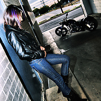 Young woman posing in leather jacket and jeans with motorcycle.