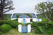 Quaint traditional highland cottage in patriotic blue and white colours to match Scottish flag, near Linicro in the Highlands of Scotland