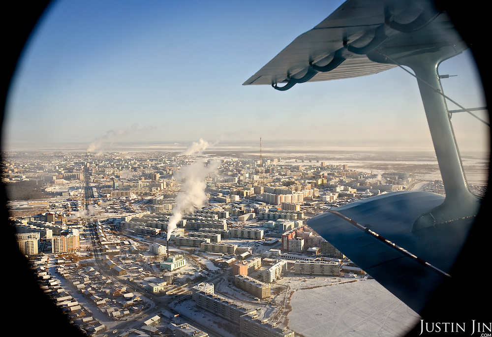 An overview of Yakutsk from a plane that takes passengers across the river Lena. River ice prevents boats from crossing, but the ice is too thin at this time of the year for cars to drive on.
