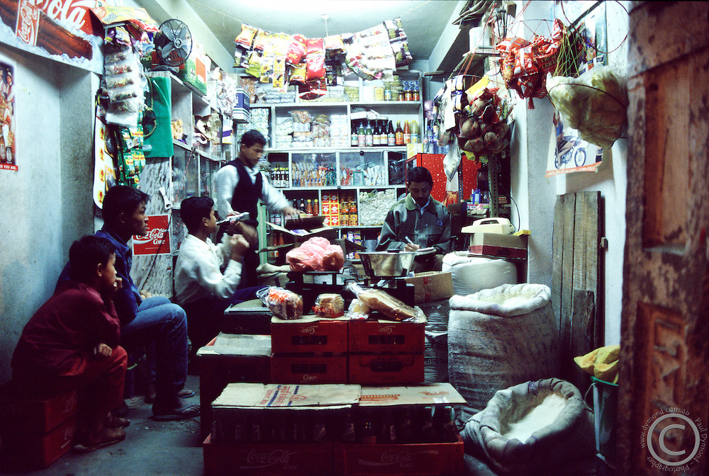A family gathers in its tiny shop in the Thamel tourist district of Kathmandu, Nepal