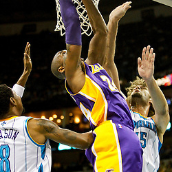 Dec 5, 2012; New Orleans, LA, USA; Los Angeles Lakers shooting guard Kobe Bryant (24) shoots over New Orleans Hornets center Robin Lopez (15) and shooting guard Roger Mason Jr. (8) during the first quarter of a game at the New Orleans Arena.  The Lakers defeated the Hornets 103-87.  Mandatory Credit: Derick E. Hingle-USA TODAY Sports