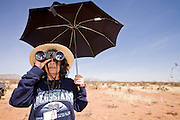 02 APRIL 2006 - THREE POINTS, AZ: DELILAH THURMAN, a Minuteman volunteer from Tucson, AZ, uses an umbrella for shade while she scans the desert for signs of illegal immigrants during the Minuteman Project action on Elkhorn Ranch Rd. between Three Points, AZ, and Sasabe, AZ, about 60 miles south of Tucson, AZ, April, 2, 2006. Volunteers from the Minuteman Project have set up lines of observation posts on remote county roads in the desert southwest of Tucson to monitor the area for illegal immigrant traffic. On Saturday night, the first night of the action, Minuteman volunteers spotted more than 50 illegal immigrants and claim their tips to the US Border Patrol led to the apprehension of at least 16 of those immigrants.  Photo by Jack Kurtz